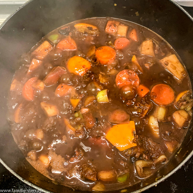 it Rotwein abgelöschtes angeröstetes Suppengemüse im Gußtopf