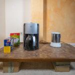 improvisierte Teeküche - ein Holzbrett mit Kaffeemaschine und Wasserkocher auf kleinen Paketen, die als Tischfüße dienen