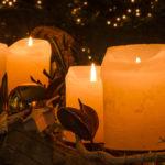 vier brennende Kerzen auf einem Weihnachtsgesteck