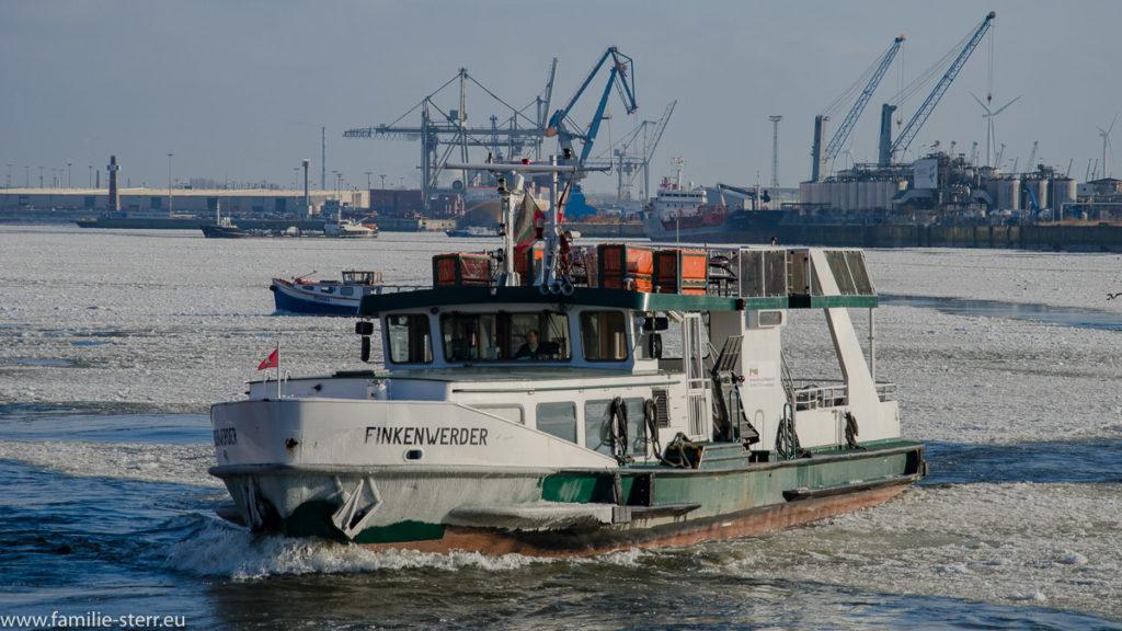 eine Hafenfähre fährt über die vereiste Elbe im Hafen bei St. Pauli