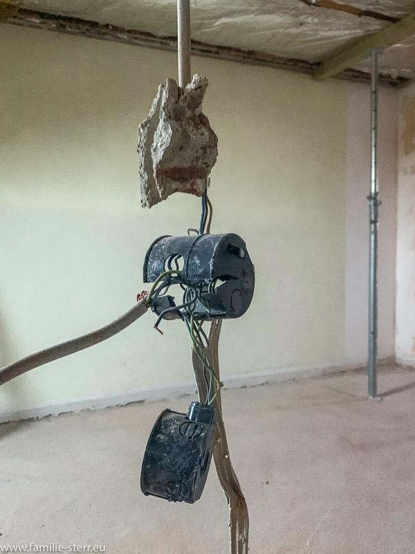 Kabelreste und kaputte Dosen nach dem Abbruch einer Wand