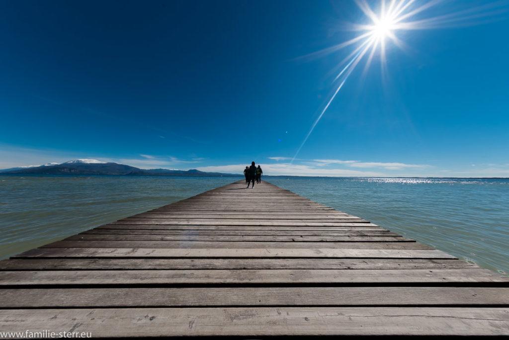 ein langer Steg führt über den See direkt auf die strahlende Sonne zu, im Hintergrund erhebt sich am anderen Ufer ein schneebedeckter Berg