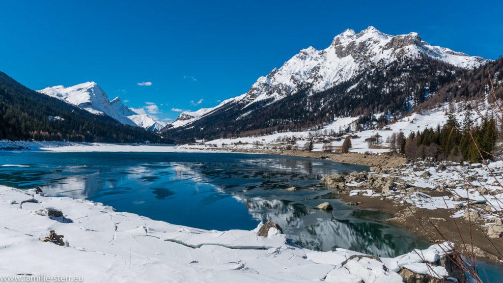 Bergsee vor verschneiten Alpengipfeln
