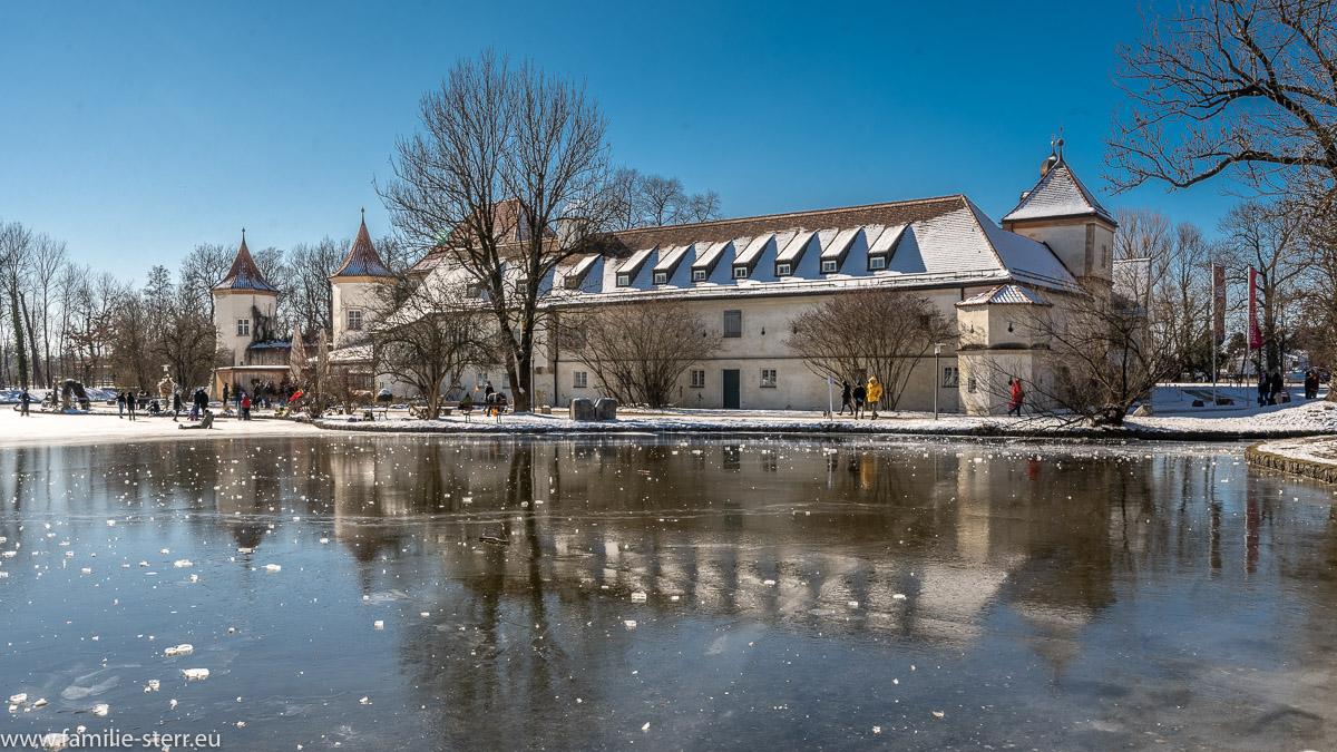 das Schloss Blutenburg spiegelt sich im Eis des zugefrorenen Schlossteichs an einem eiskalten Wintertag