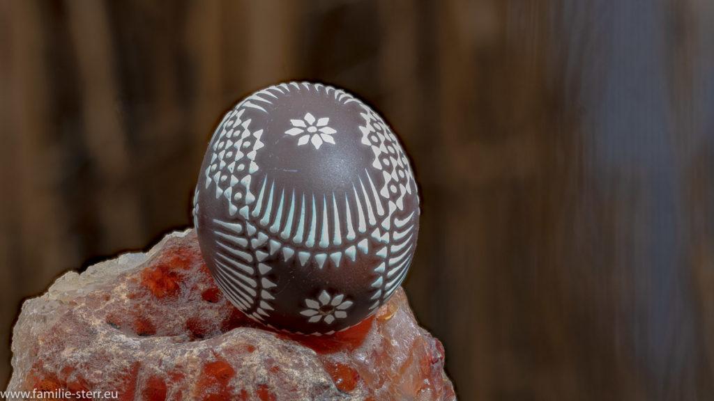braun - weiß bemaltes serbisches Osterei auf einem Stein