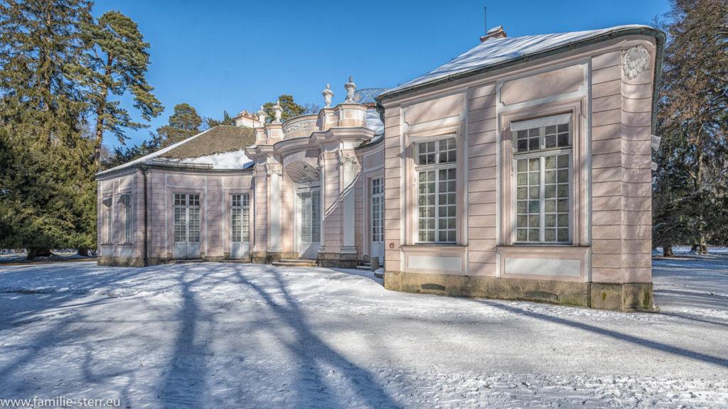 das Jagdschloss Amalienburg im winterlichen Schlosspark unter strahlend blauem Himmel