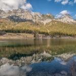die Berge und der weißblaue Himmel spiegeln sich dem ruhigen Wasser des Hintersees bei Ramsau im Berchtesgadener Land