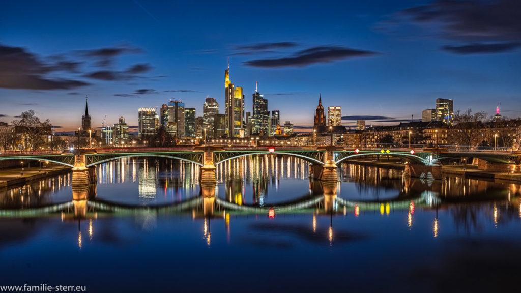nächtlicher Blick über den Main auf das Bankenviertel mit den Hochhäusern in Frankfurt am Main zur blauen Stunde