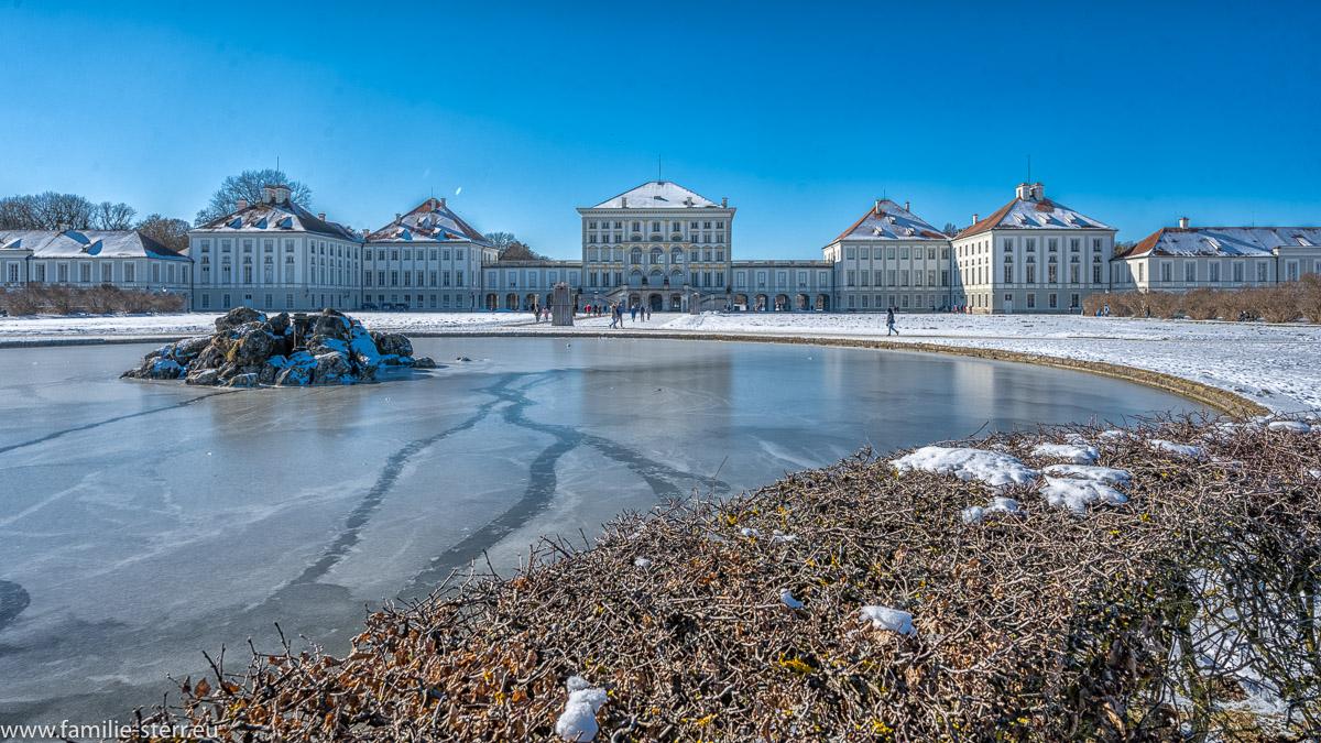 Fontäne und Ehrenhof vor dem Schloss Nymphenburg an einem strahlend blauen Wintertag
