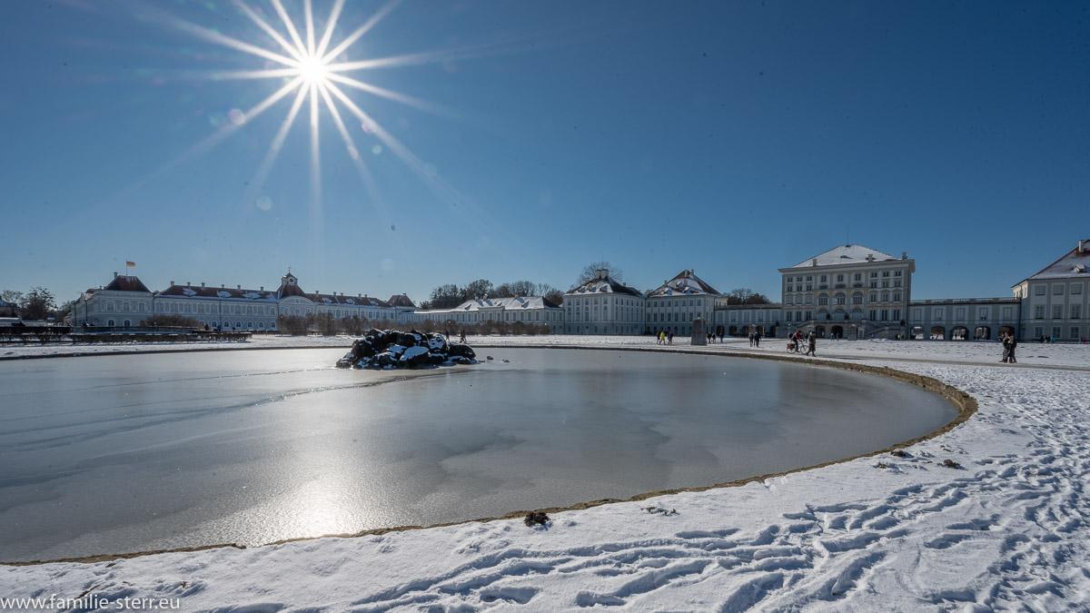 strahlende Sonne am blauen Himmel über dem winterlichen Schluss Nymphenburg
