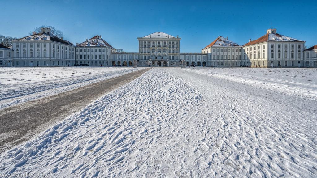 strahlend blauer Himmel über dem schneebedeckten Ehrenhof vor dem Schloss Nymphenburg