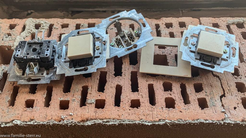 alte Steckdosen und Schalter auf einem Ziegelstein