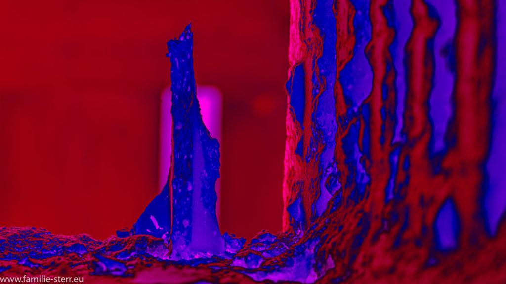 abstrakte Darstellung eines spitzen Steines in rot und blau