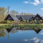 drei Holzhäuser in Form eines Spreewälder Dreiseitenhofs spiegeln sich im Naturbadeteich des Seehotels Burg Spreewald