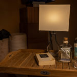 kleine Lampe, Gin, Tonicwasser, ein Glas und ein Buch auf einem Teakholztablett vor Baumaterial auf der Baustelle