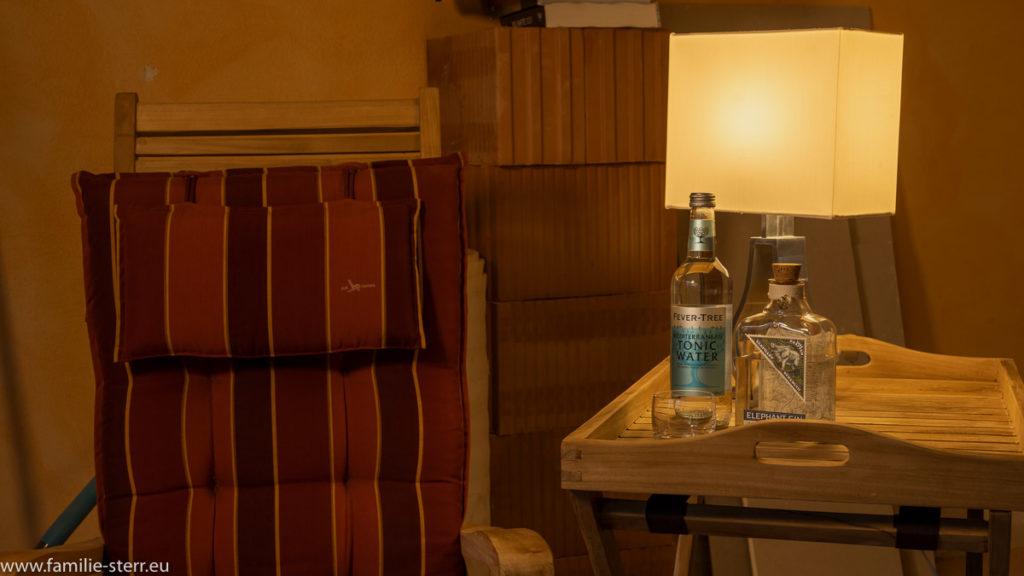 kleine Lampe, Gin, Tonicwasser, ein Glas und ein Buch auf einem Teakholztablett vor Baumaterial auf der Baustelle neben einem Deckchair