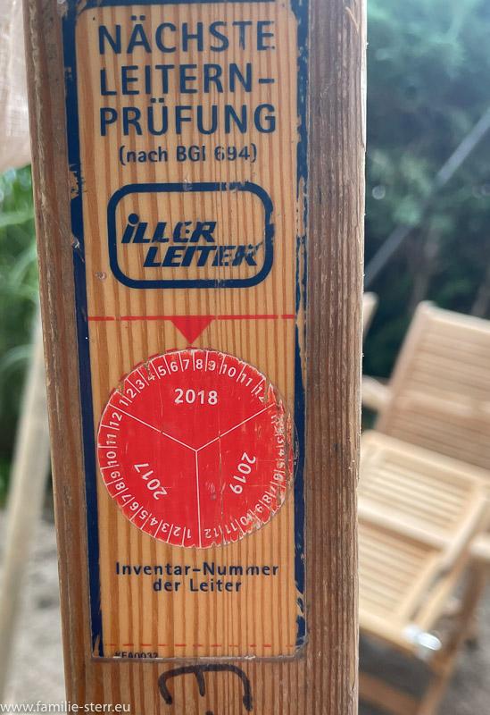 Aufkleber auf einer Holzleiter mit Hinweis auf die fällige Leiterprüfung