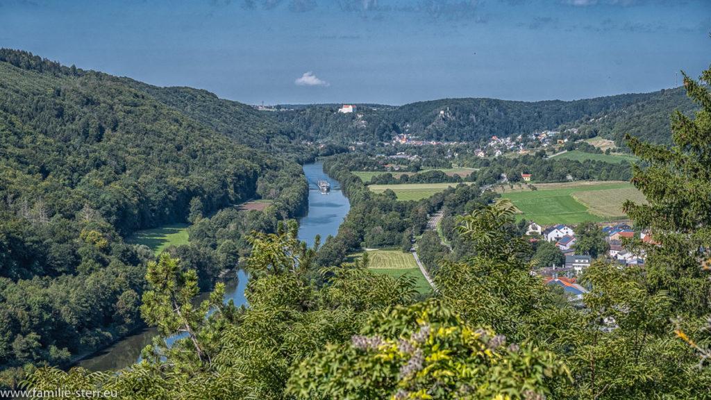 Blick von der Burg Prunn über den Main-Donau-Kanal, im Hintergrund liegt Riedenburg mit dem Schluss Rosenburg, auf dem Kanal fährt ein großer Ausflugsdampfer