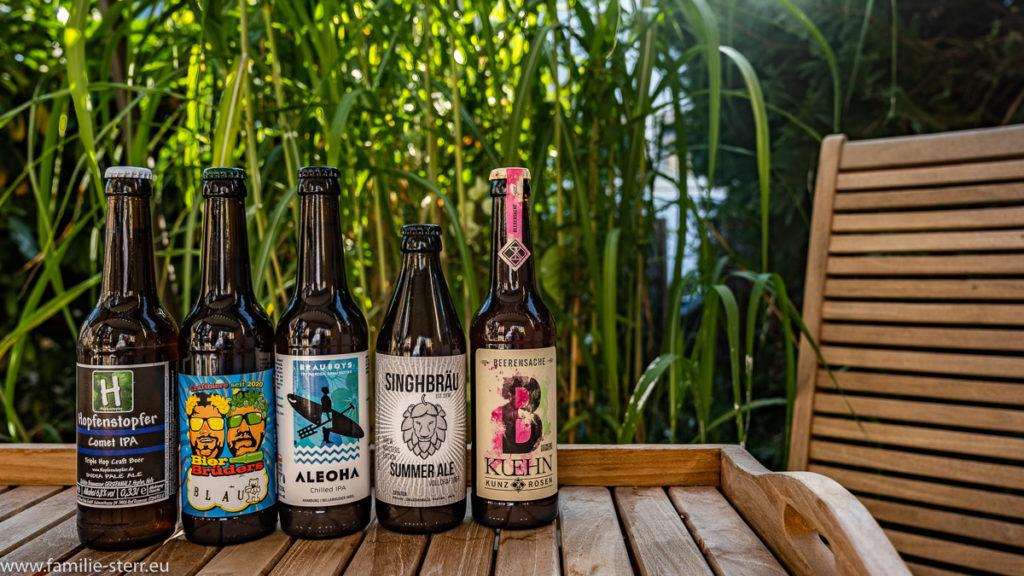 5 Flaschen Kraft-Beer im vor grünem Schilf im Garten