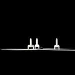 Gewindelaschen aus einem Fliese-Nivellliersystem in einem Lichtstrahl